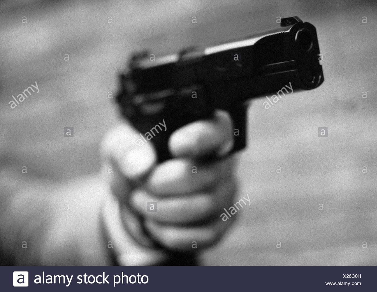 Hand holding gun, close-up, b&w - Stock Image