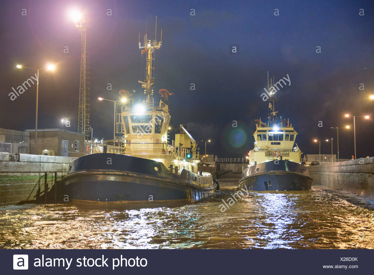 Tugboats docked in harbor at night - Stock Image