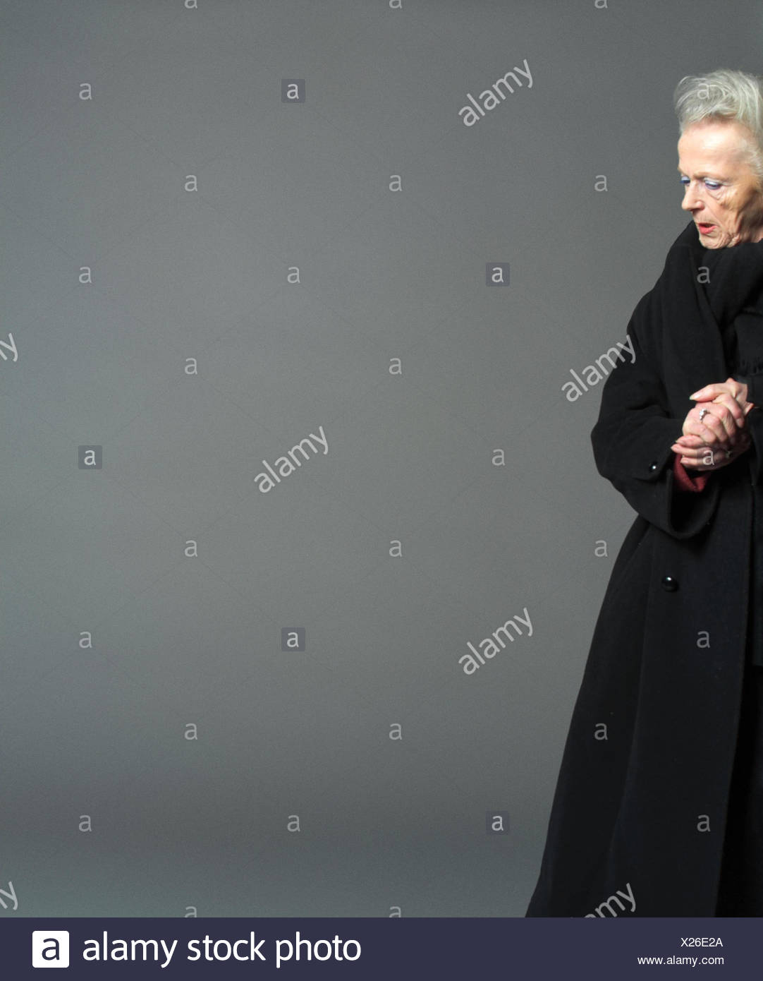 Senior, winter clothes, seriously, surprises, detail, very close, studio, pensioner, woman, old, grey-haired, casing, surprise, dismays, dismay, grief, dealts with, worried, stand, side view - Stock Image