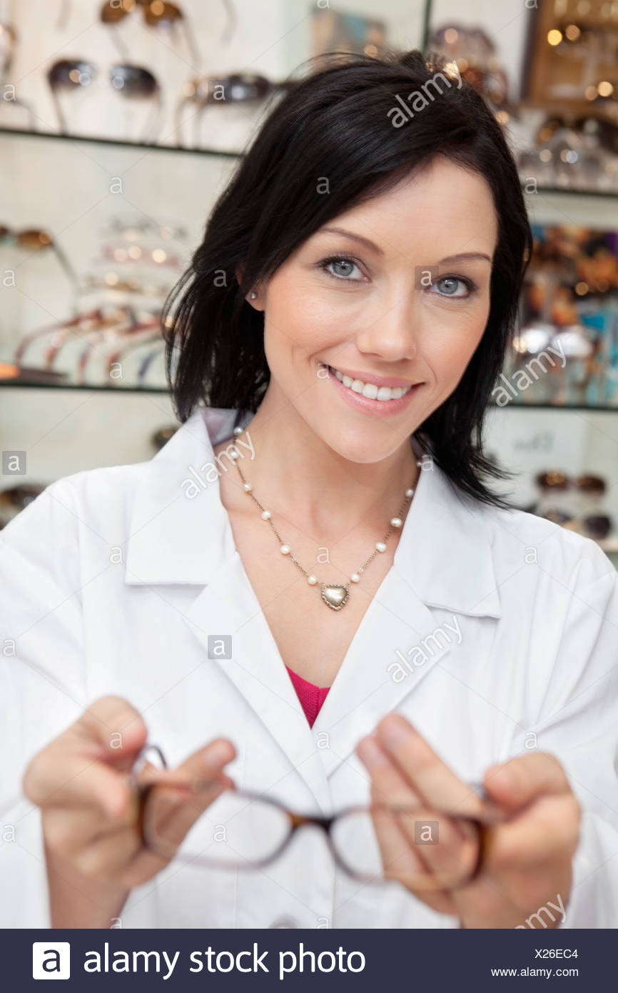 Portrait of a happy mid adult eye specialist holding glasses - Stock Image