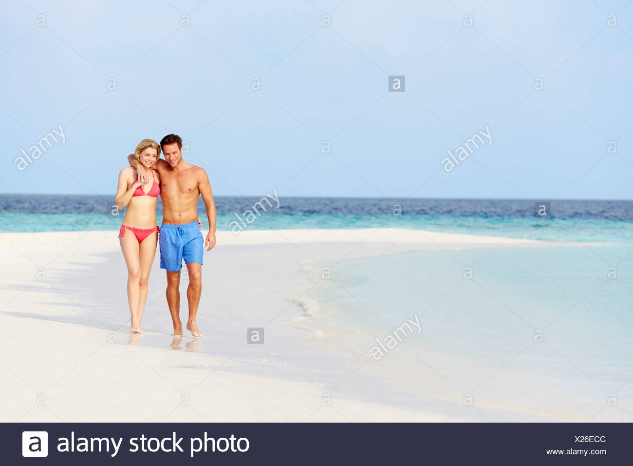 Romantic Couple Walking On Beautiful Tropical Beach - Stock Image