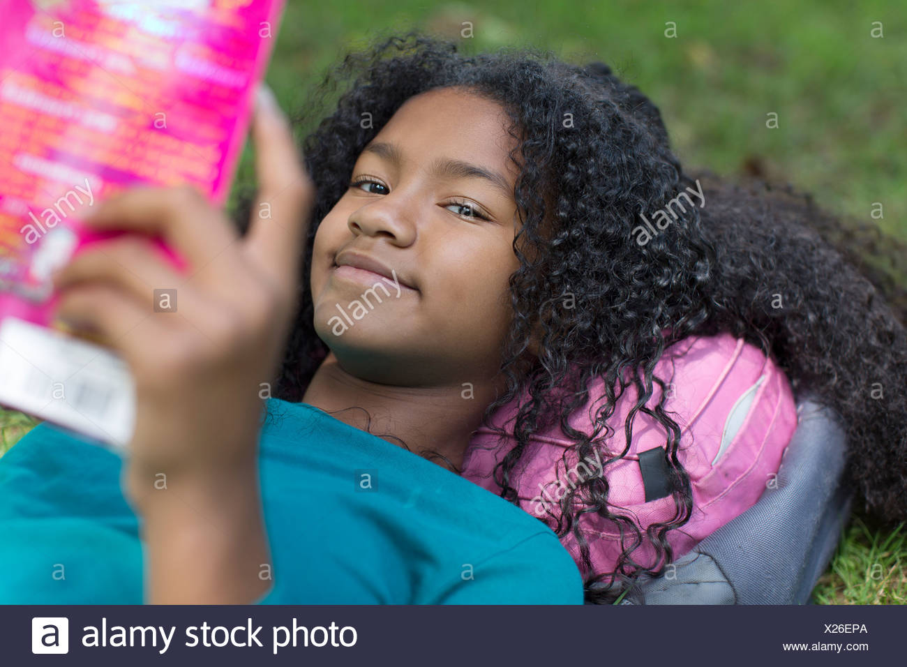 Close up portrait of young girl reading in park - Stock Image