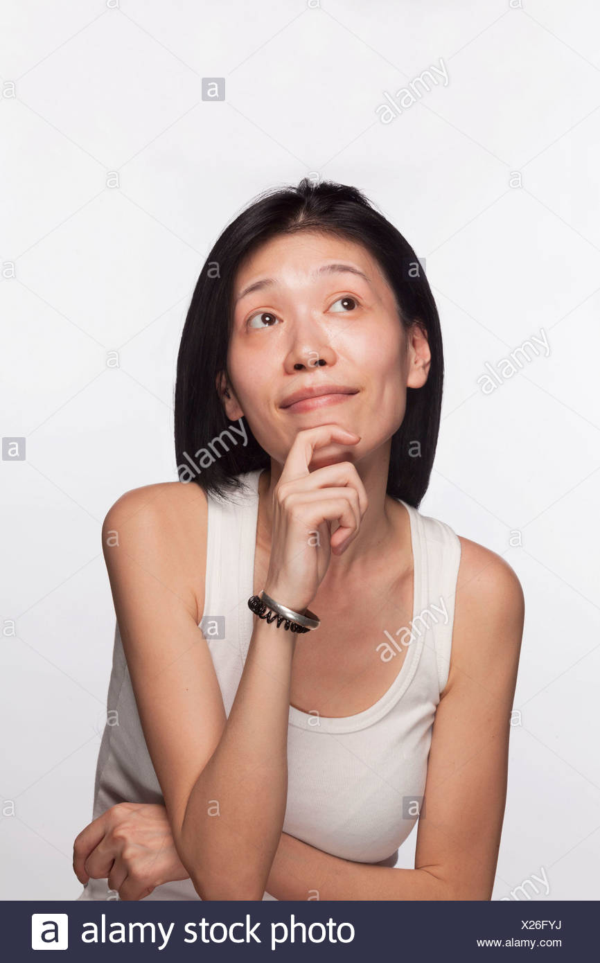 Portrait of woman with hand on her chin looking up in contemplation - Stock Image