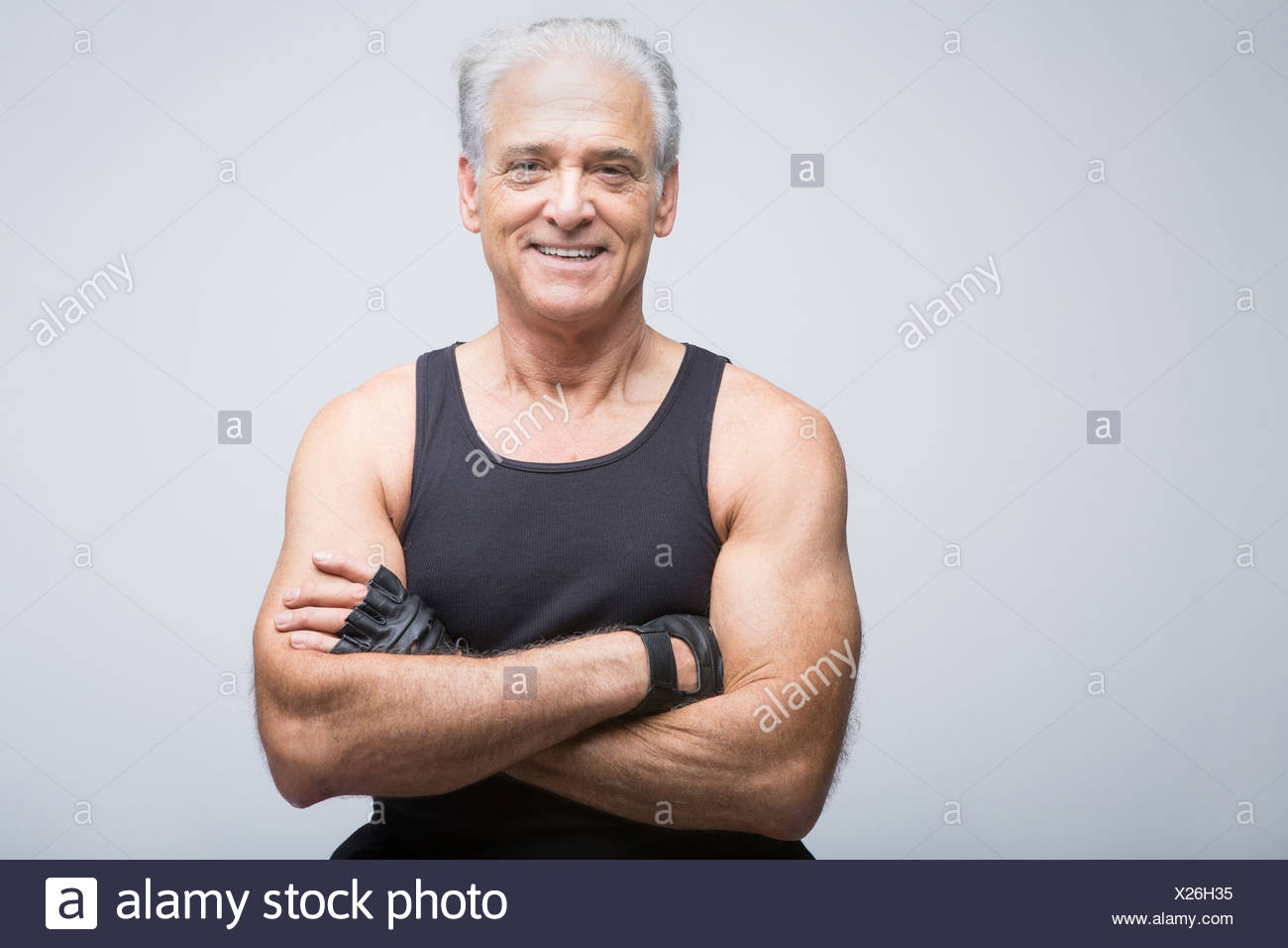 Senior man in sports clothing with arms crossed, portrait - Stock Image