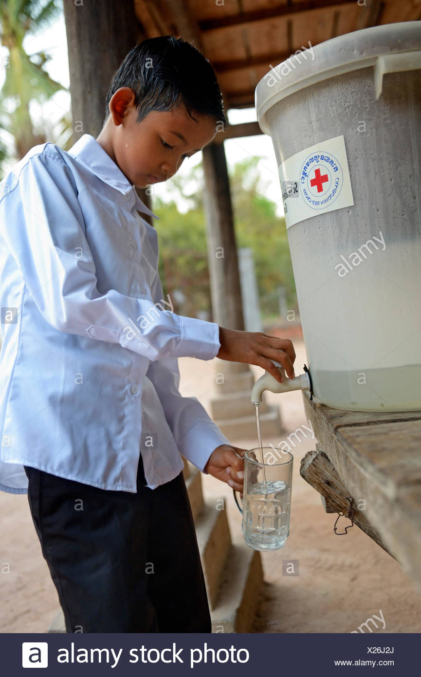 Boy drinking filtered water, the water filter has been distributed as part of a hygiene campaign from a charity, Lompong Commune - Stock Image
