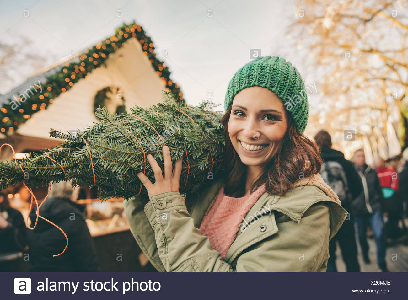 Happy woman with a wrapped-up tree walking over the Christmas Market - Stock Image