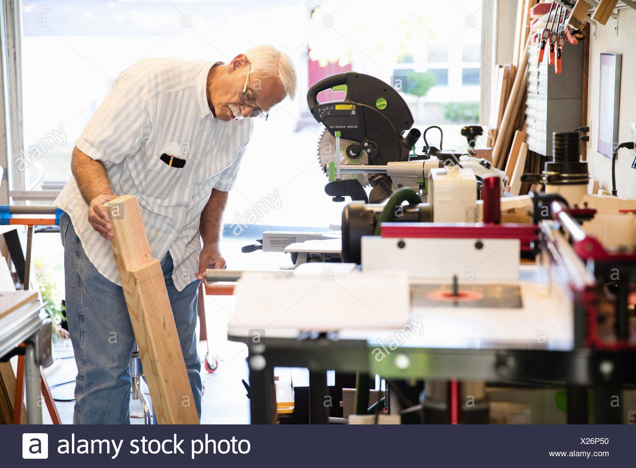 Senior man checking woodblock in carpentry workshop - Stock Image