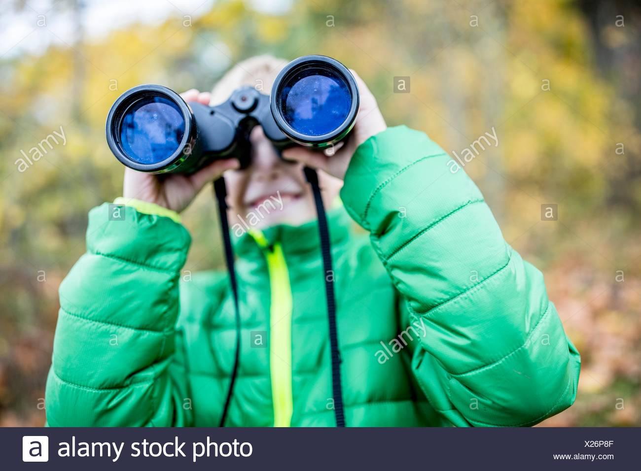 MODEL RELEASED. Boy looking through binoculars, close-up. - Stock Image