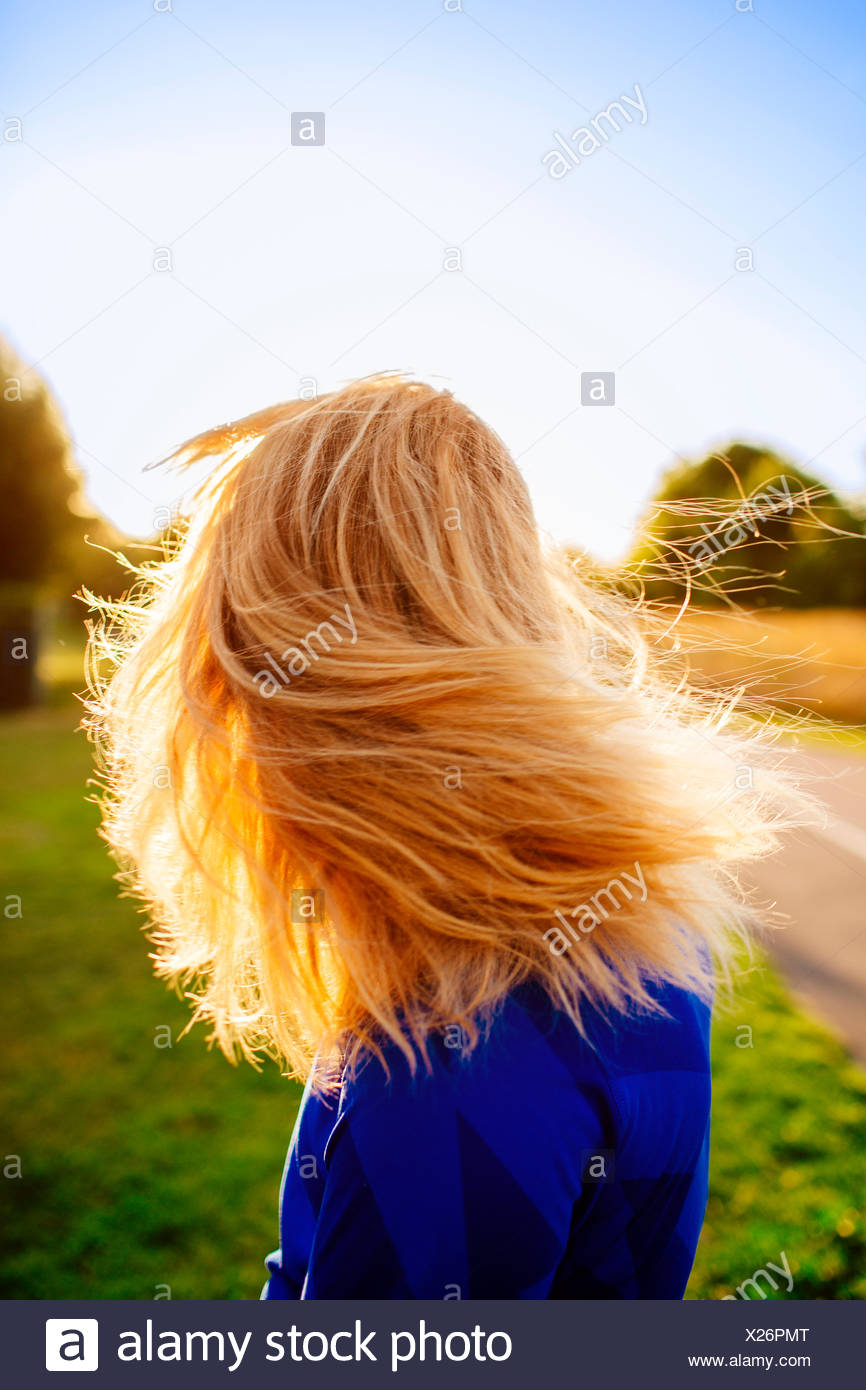 Side view of sporty woman tossing hair at park - Stock Image