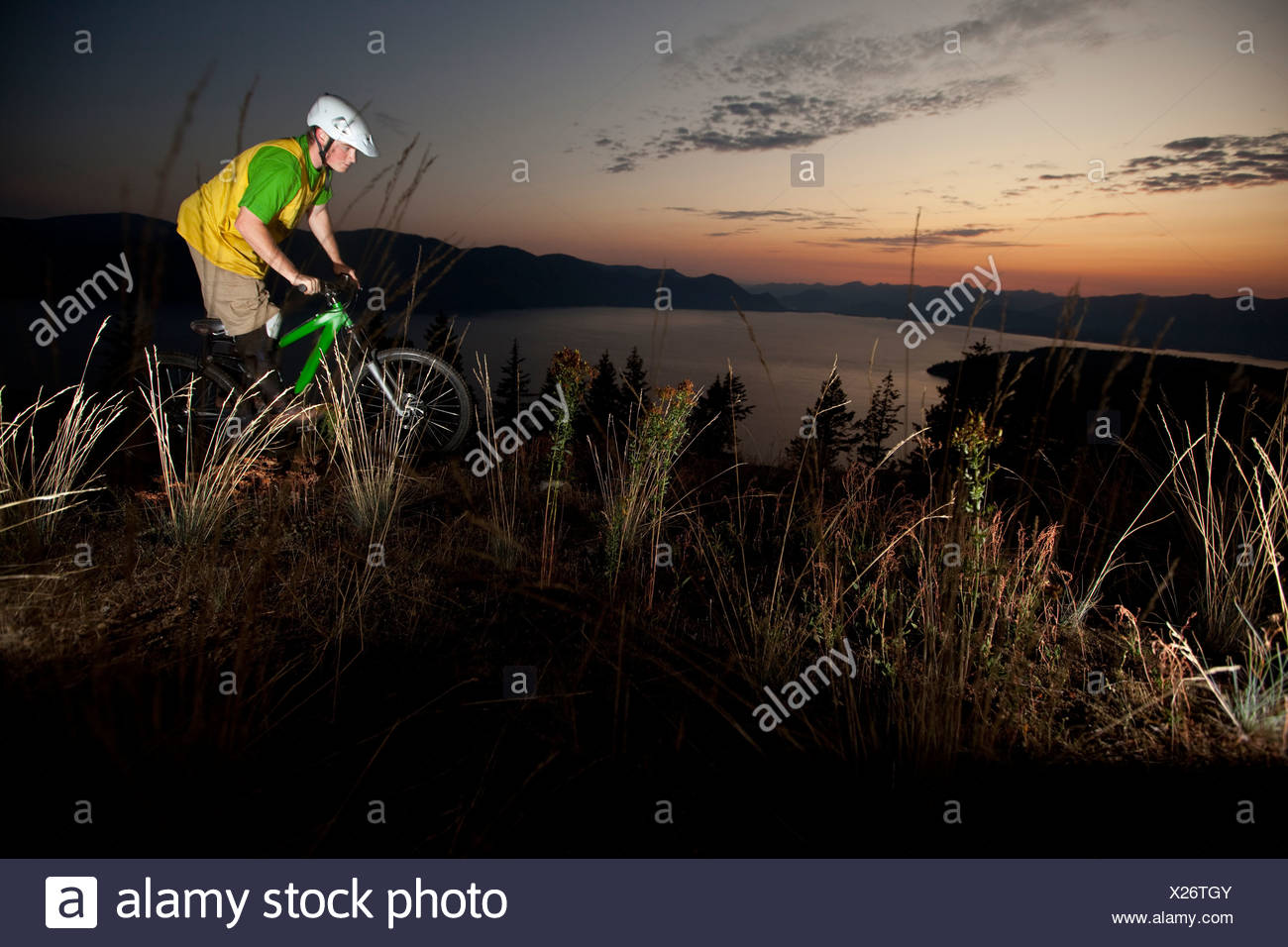 Young adult mountain biking at sunrise in Idaho. Stock Photo