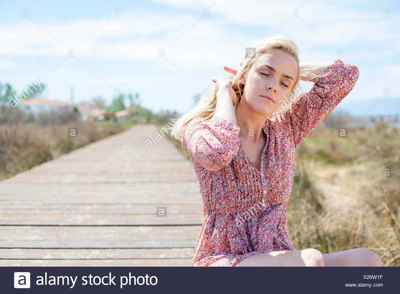 Young woman sitting on boardwalk eyes closed - Stock Image