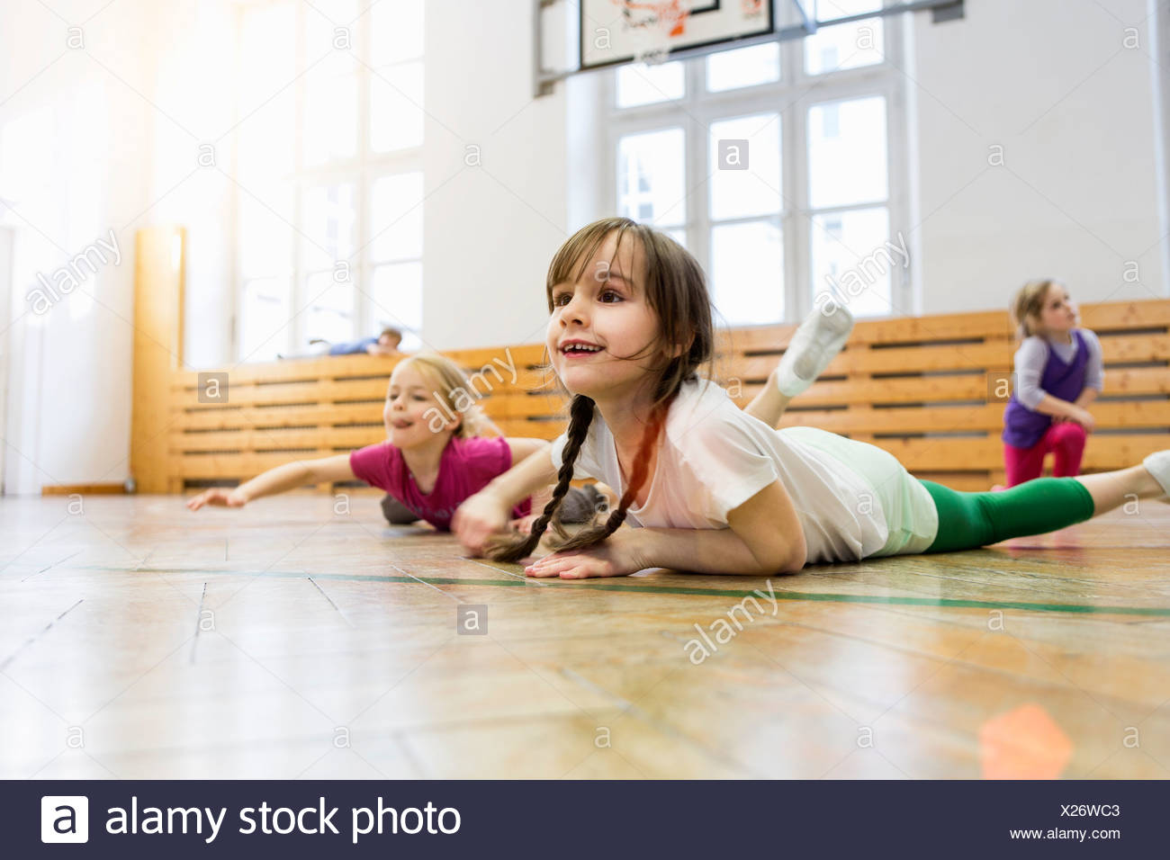 Girls lying on front in physical education class, stretching - Stock Image