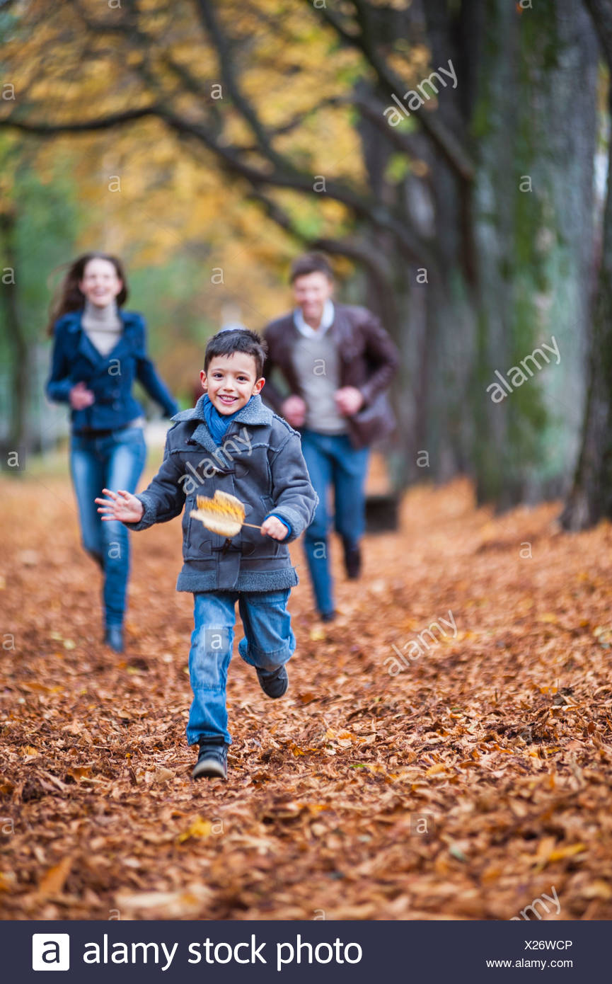 Young boy and parents running through autumn leaves in park - Stock Image