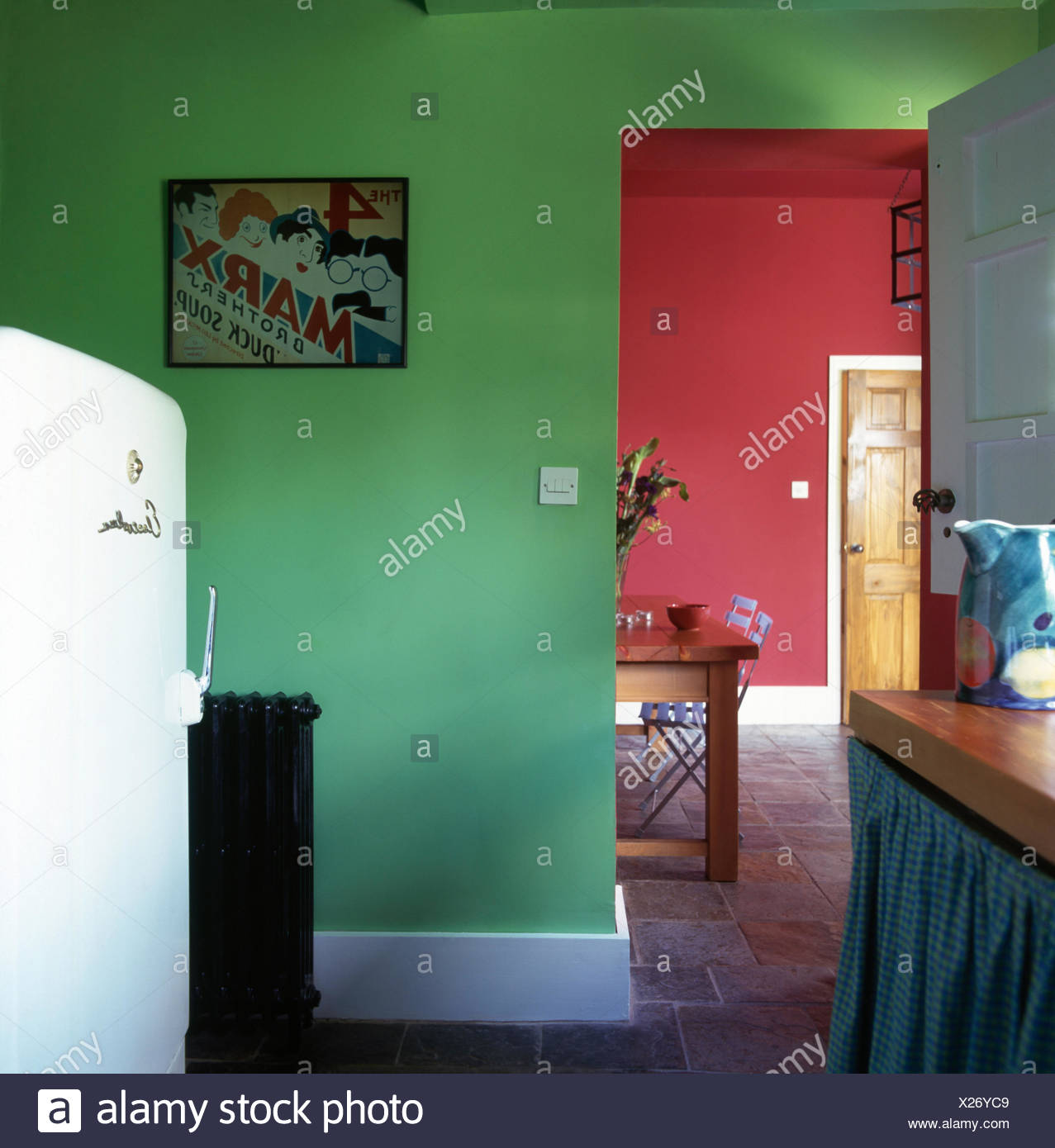 Large fridge in a bright green kitchen with doorway to a red dining room - Stock Image