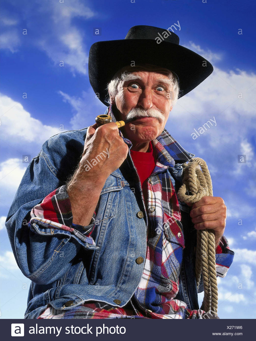 Senior, 'cowboy', whistle, lasso, facial play, decided, energetically, half portrait, cloudy sky Senior, outside, studio, man, old, denim jacket, shirt, checked, stetson, moustache, moustache, beard, hairs, white, view, seriously, determination, energy, p - Stock Image