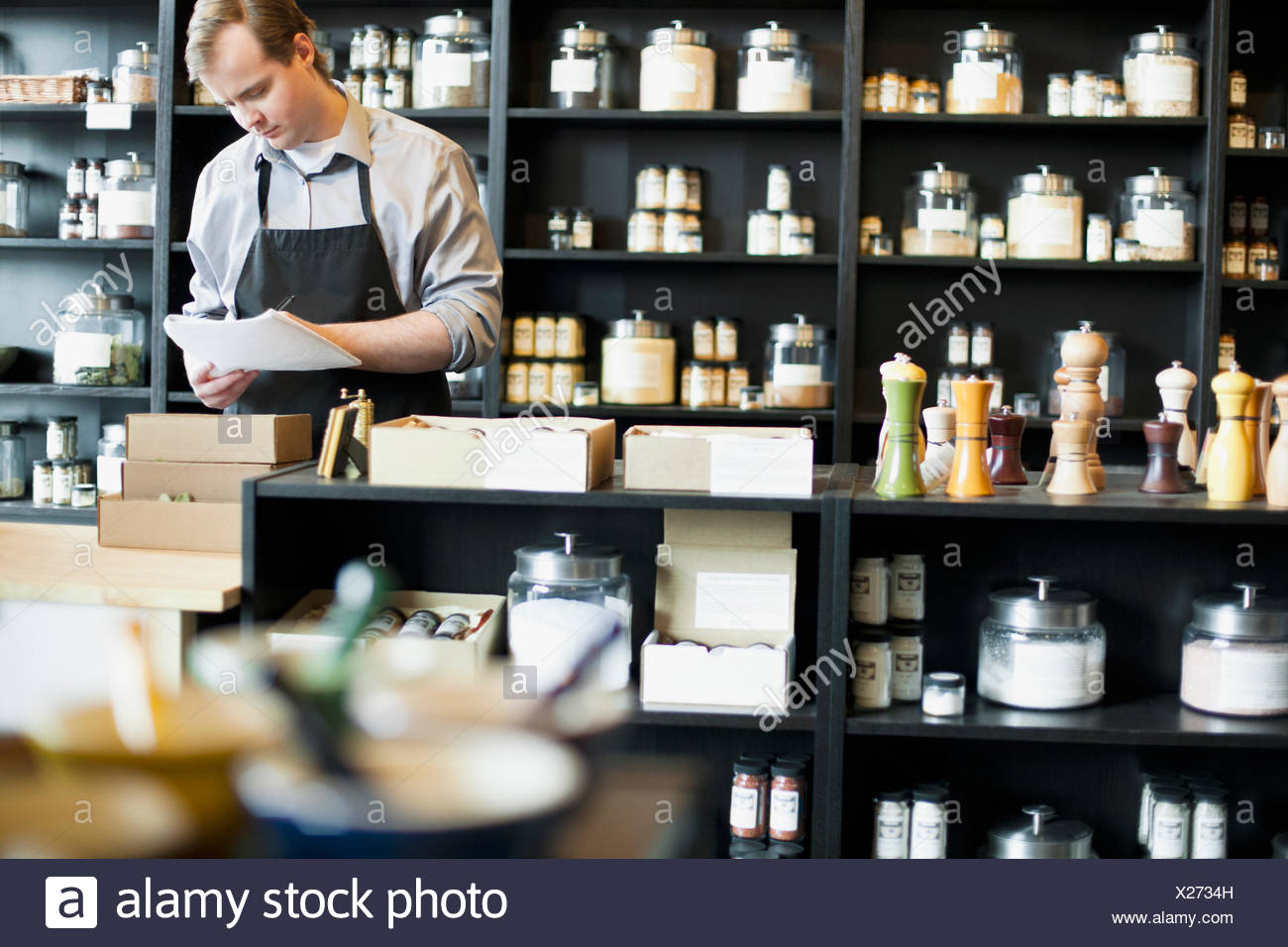 merchant doing paperwork in spice store - Stock Image