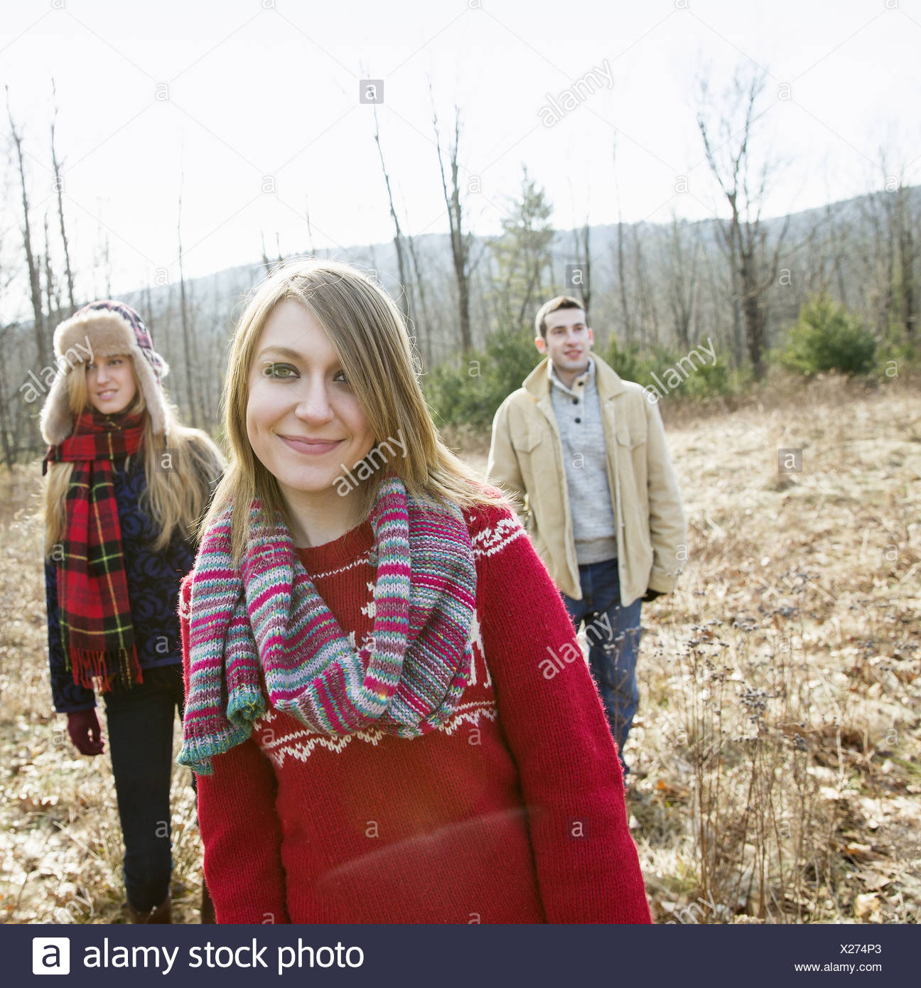 A group of three people, a man and two women, on a walk on a winter day. - Stock Image