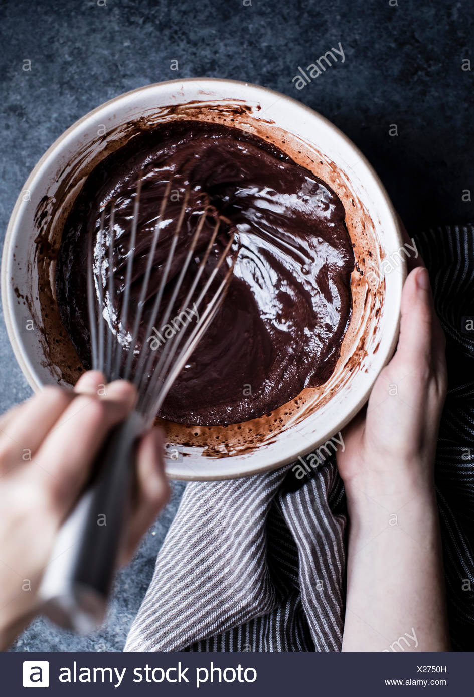 A womans hand whisking chocolate sauce in a bowl - Stock Image