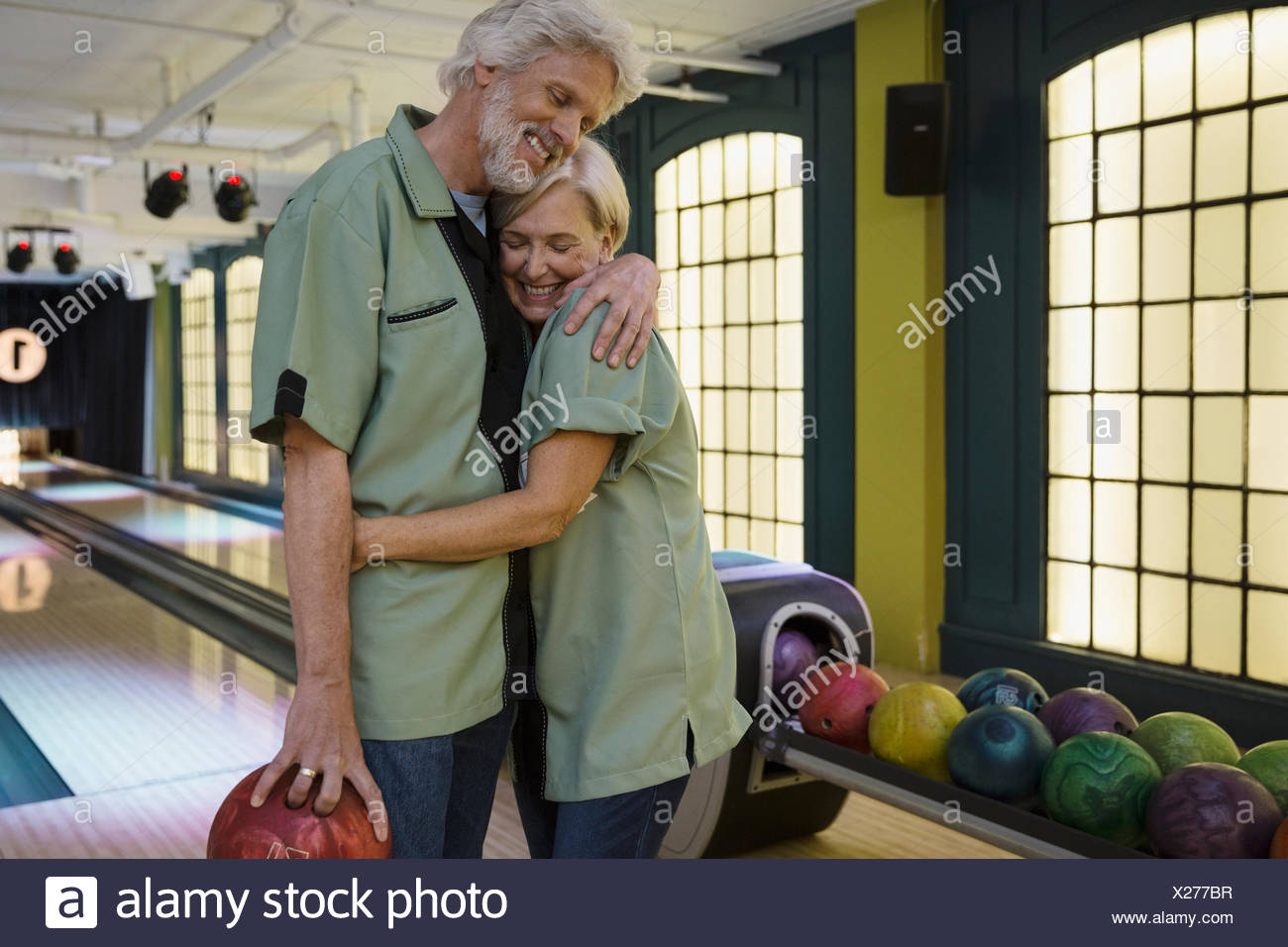 Couple in bowling shirts hugging at bowling alley - Stock Image