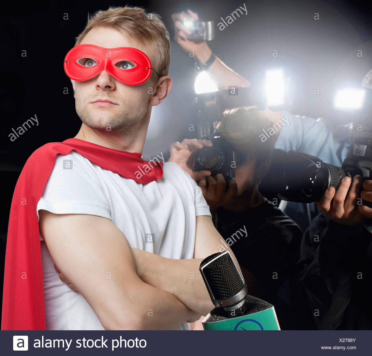 Superhero being photographed by paparazzi - Stock Image