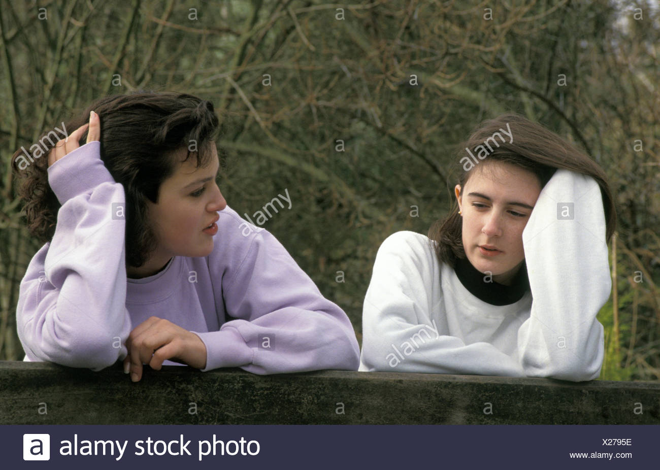two teenage girls leaning over gate having conversation - Stock Image