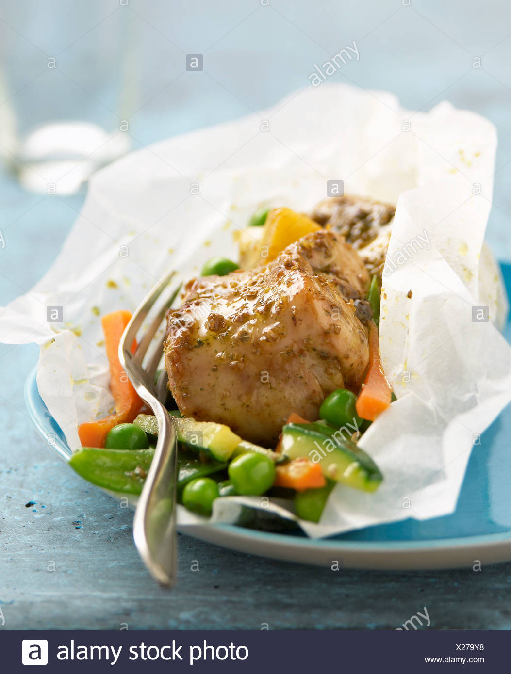 Rabbit with coriander,lemons and vegetables cooked in wax paper - Stock Image