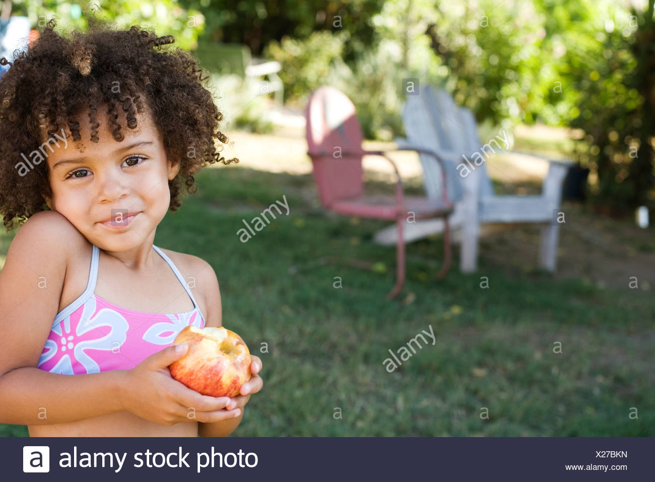 Girl in swimwear holding apple in yard - Stock Image