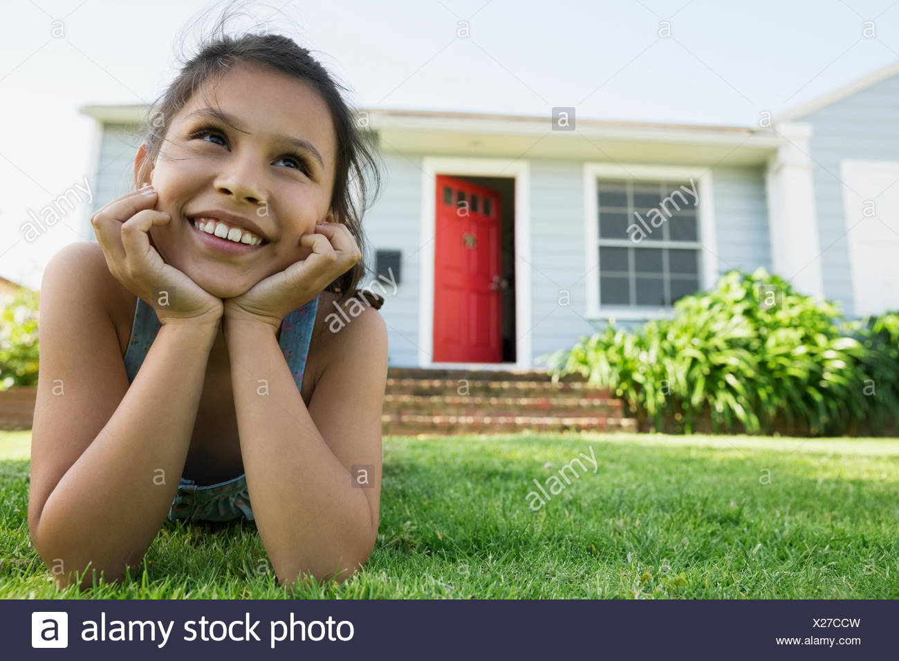 Smiling girl laying in grass in front yard - Stock Image