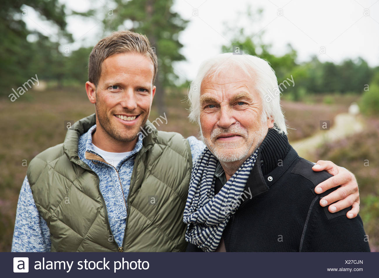 Portrait of father and adult son, smiling - Stock Image