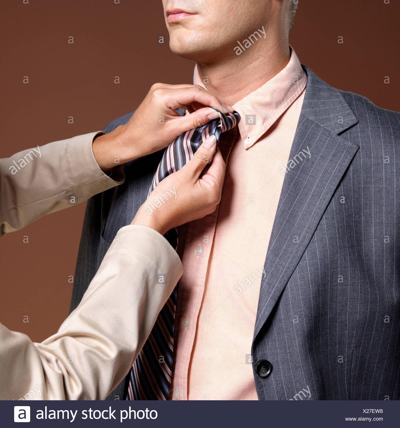 Woman binding businessman´s tie - Stock Image