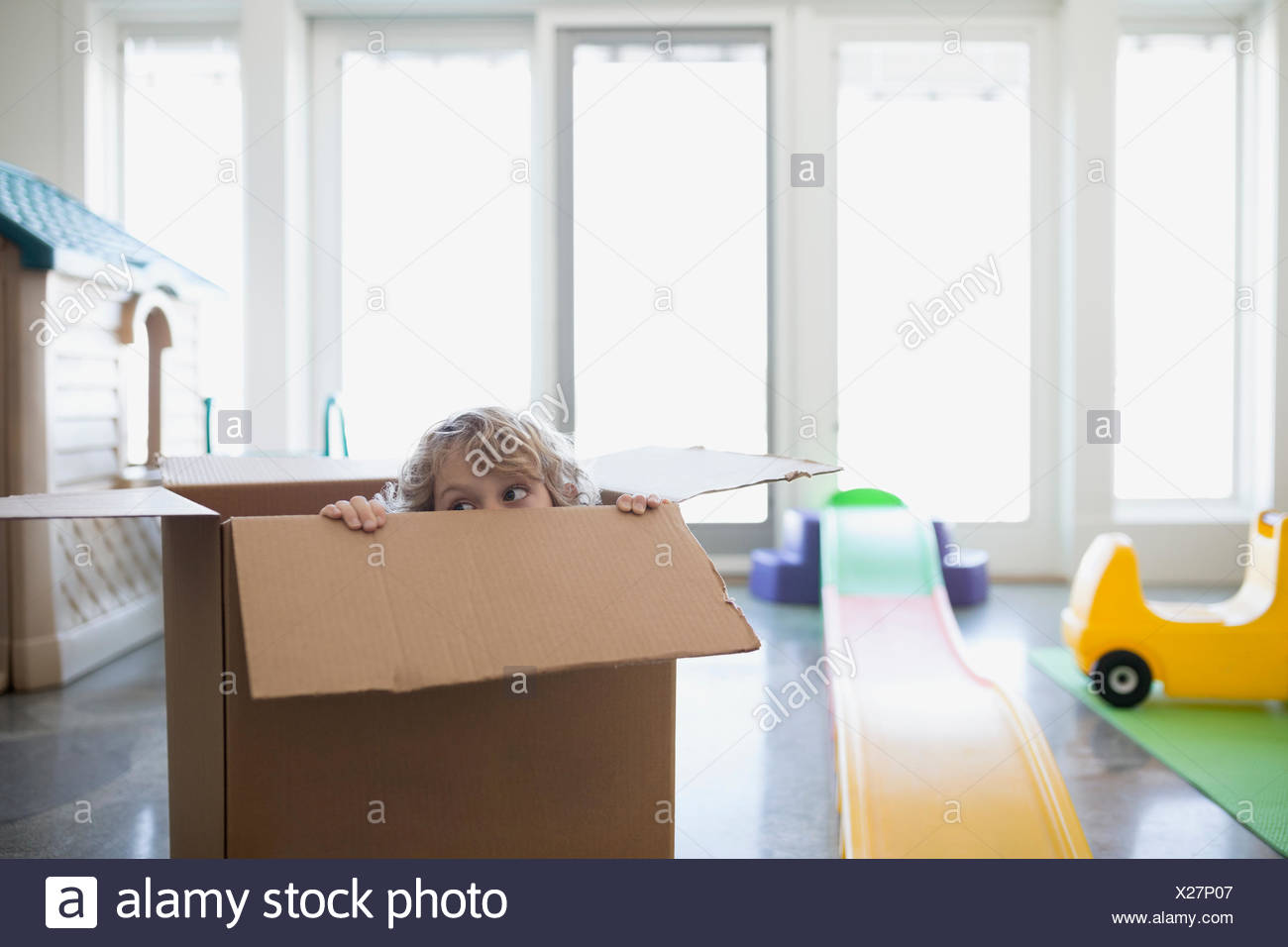 Boy hiding in cardboard box - Stock Image