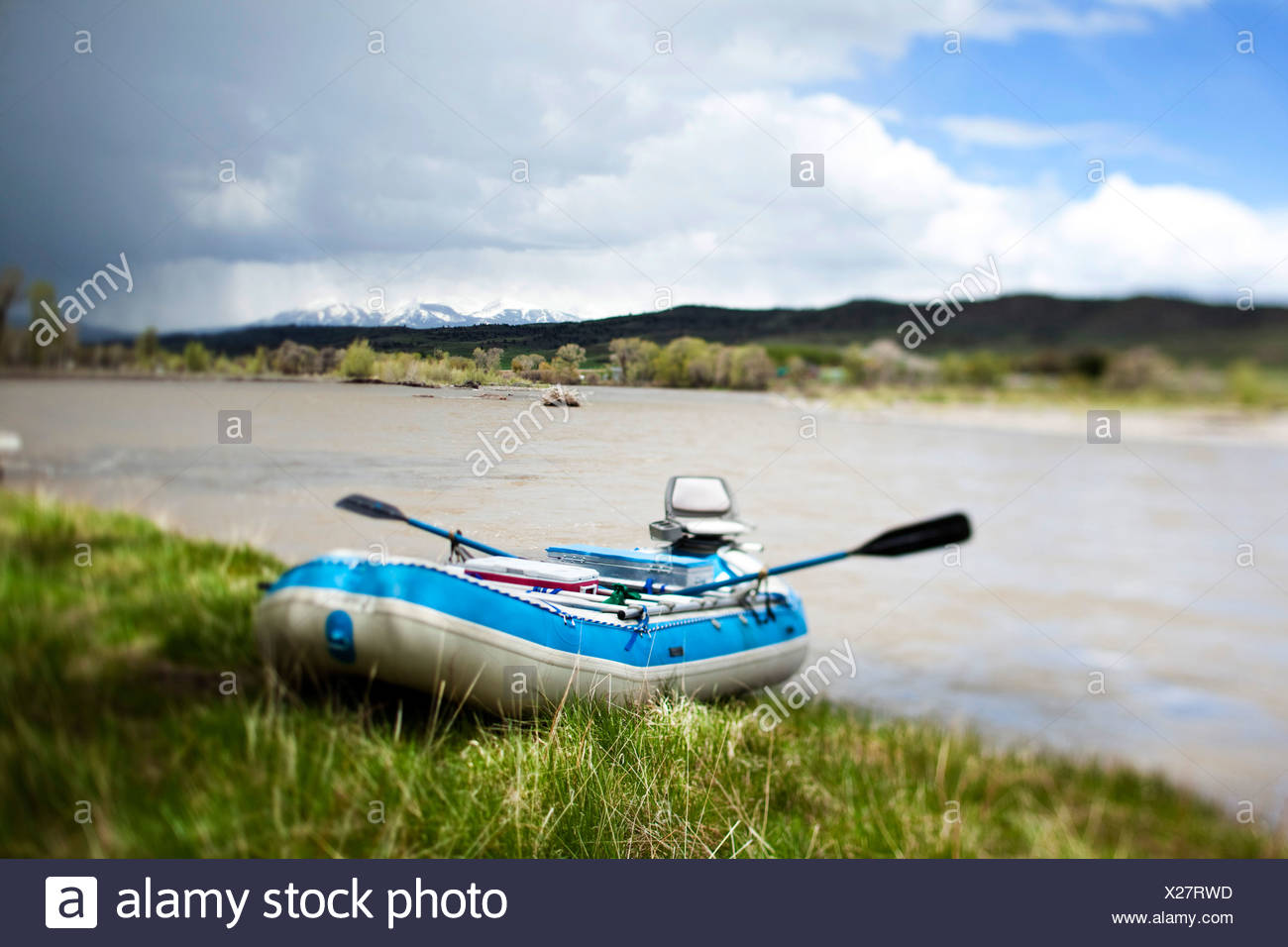 A raft sits on the banks of a river in Montana. - Stock Image