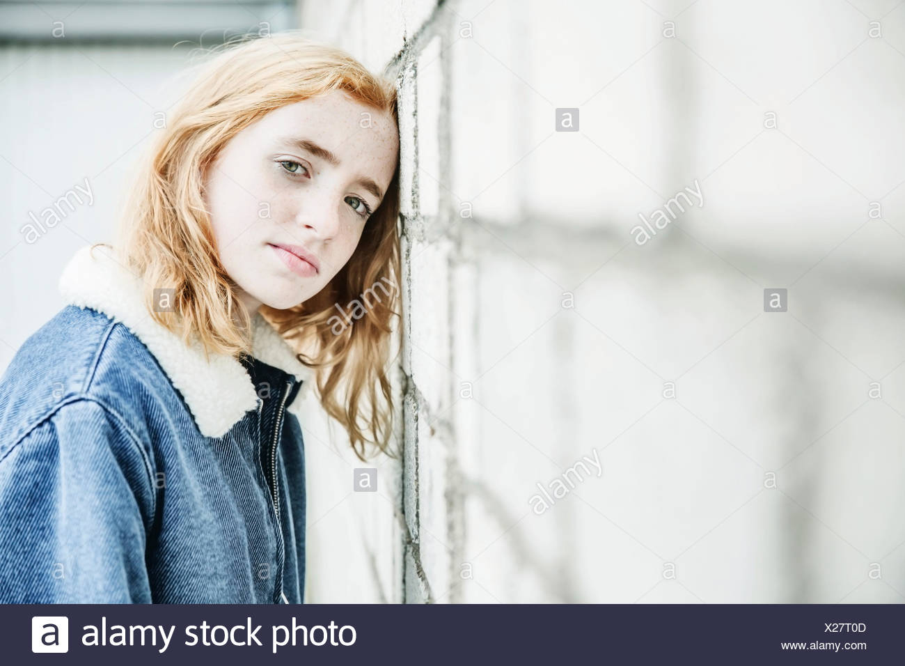 Portrait of girl leaning her head against a wall - Stock Image