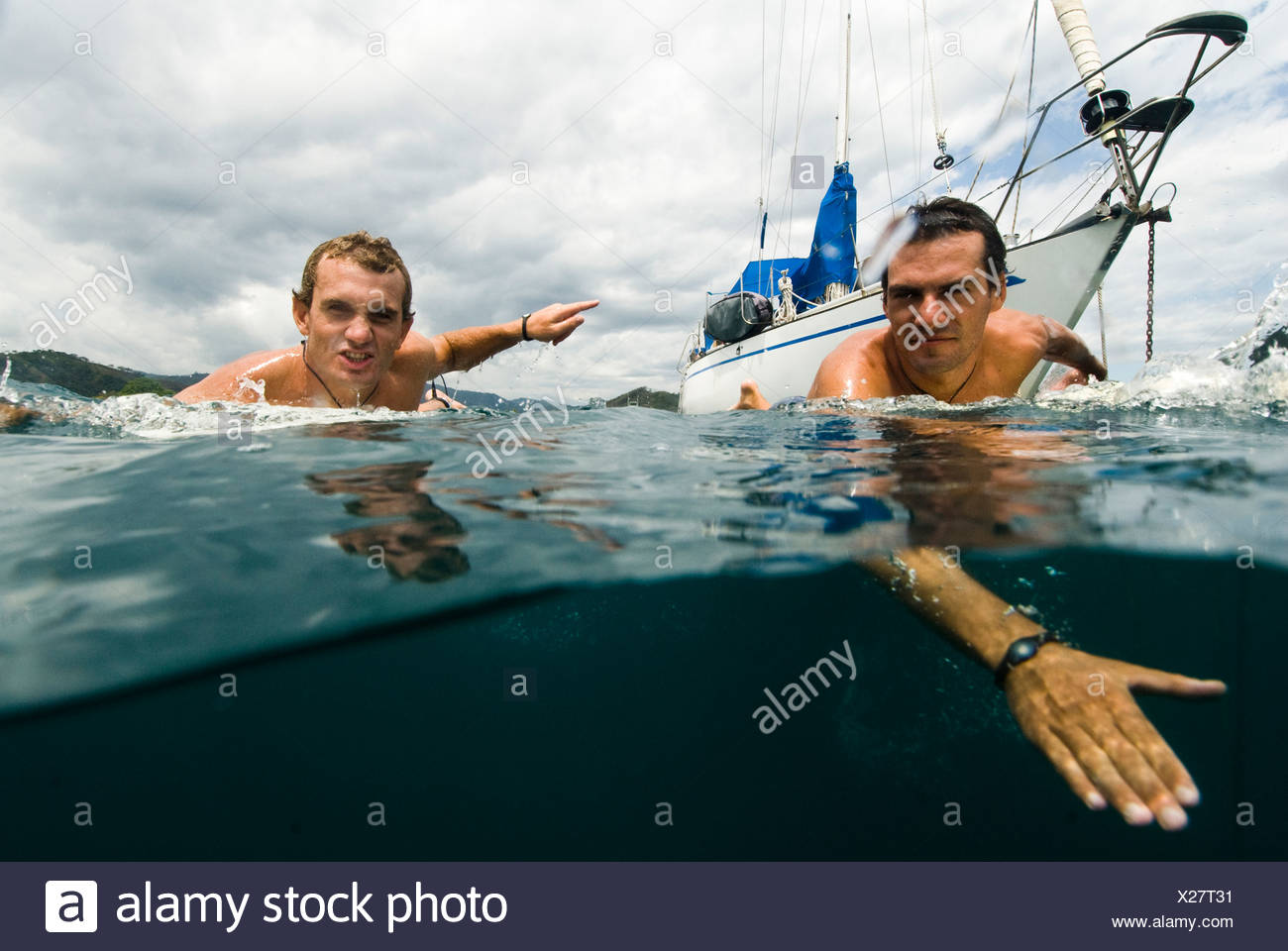 Two guys heading out for surf in Costa Rica - Stock Image