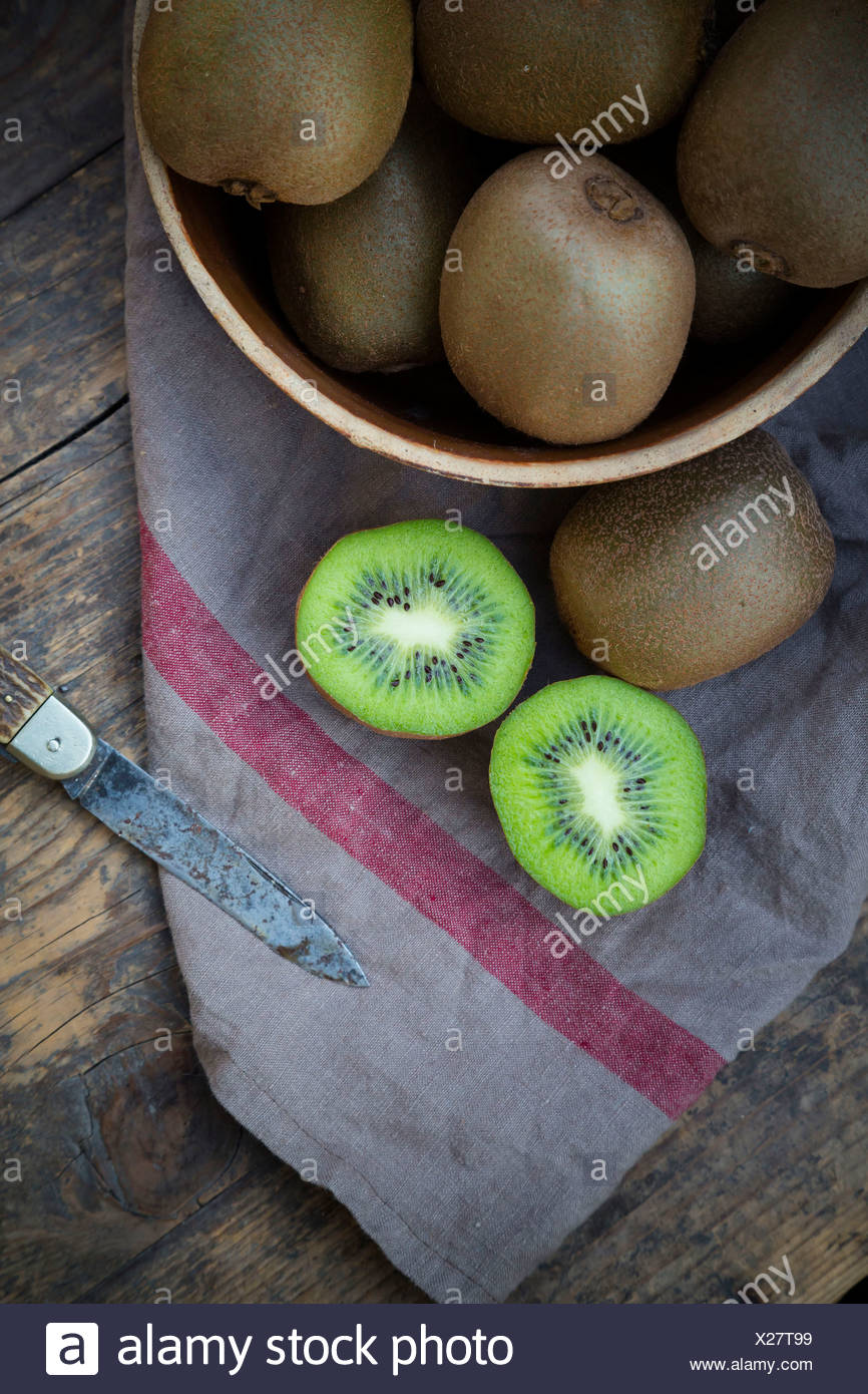 Bowl of kiwis (Actinidia deliciosa) and pocketknife on wooden table - Stock Image