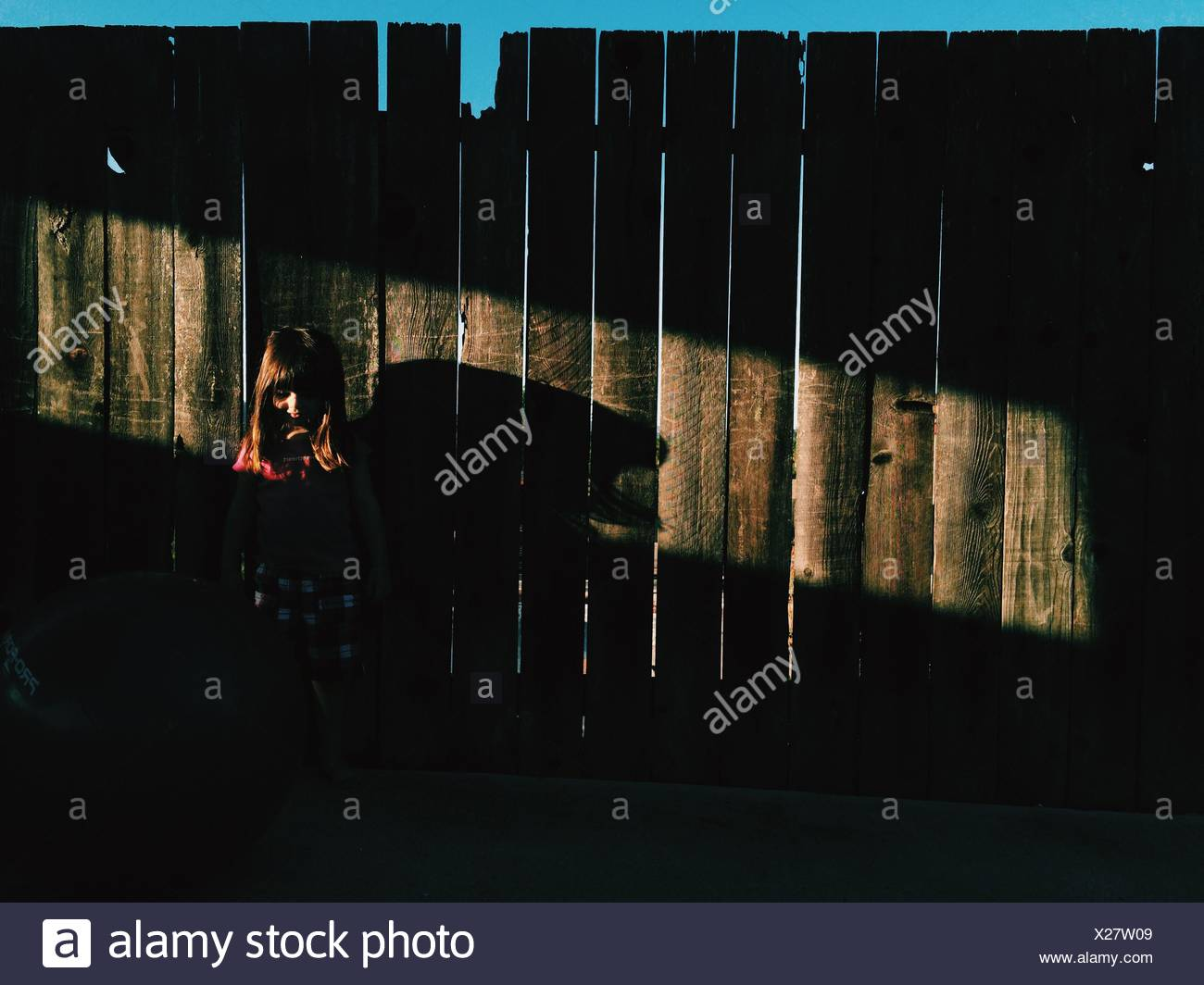 Girl Standing Against Fence - Stock Image