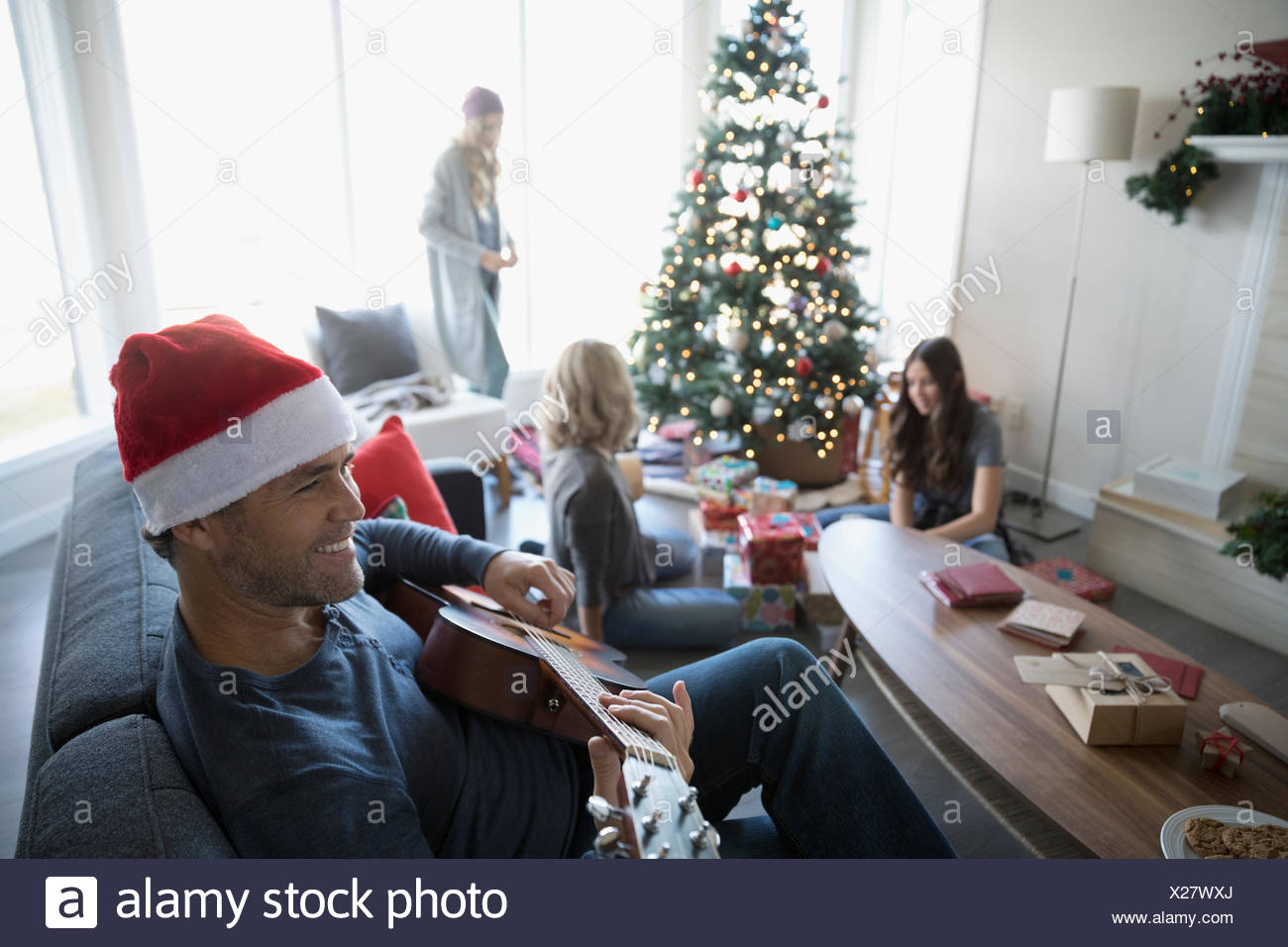Smiling father in Santa hat playing guitar while family wraps gifts in living room with Christmas tree Stock Photo