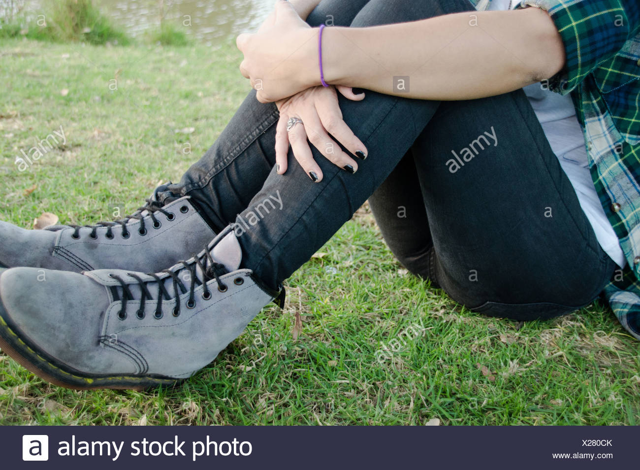 Waist down, young woman sitting on grass - Stock Image