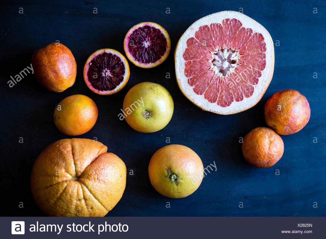 Citrus fruits and a blue background. Grapefruits, oranges, blood oranges. - Stock Image