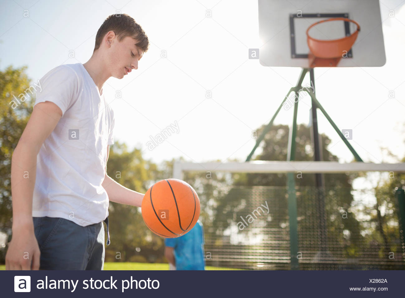Young male basketball player on court with basketball - Stock Image
