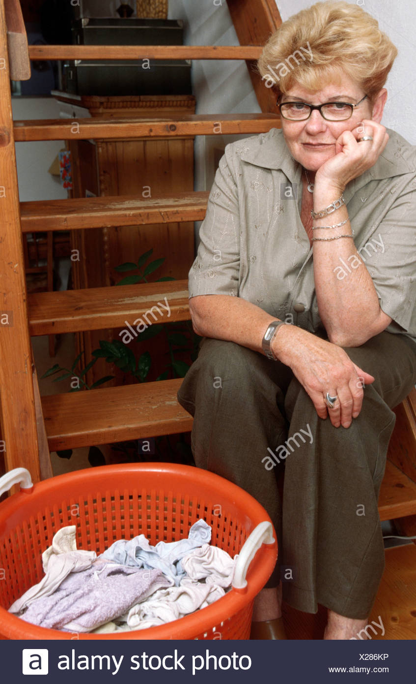 Depressed woman resting with laundry basket on stairway - One only - woman sad one person only indoors - Stock Image