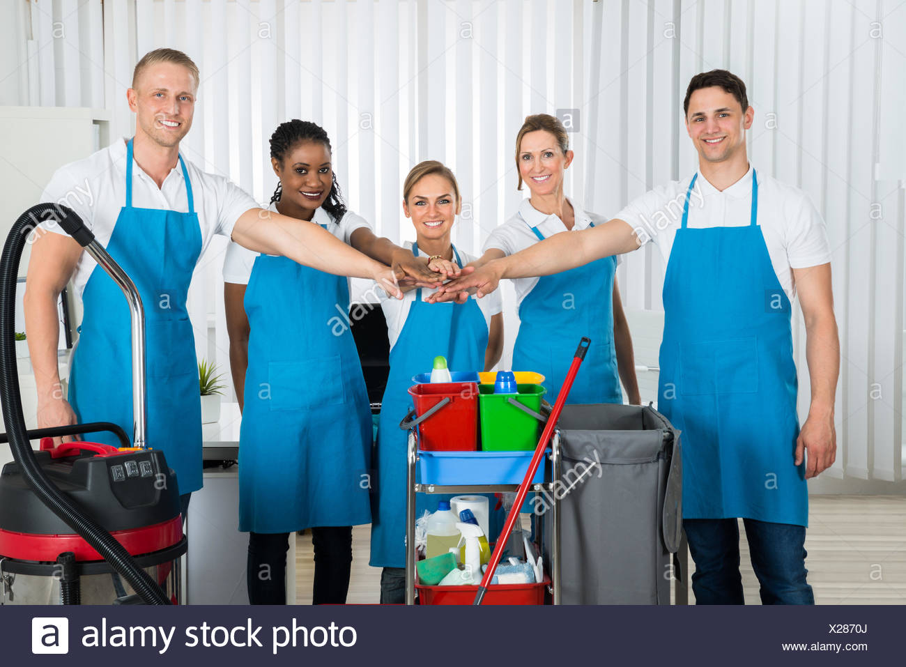 Happy Cleaners Stacking Hands - Stock Image