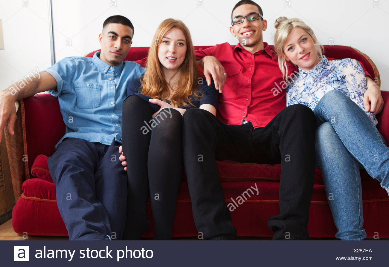 Four young adults sitting on sofa - Stock Image