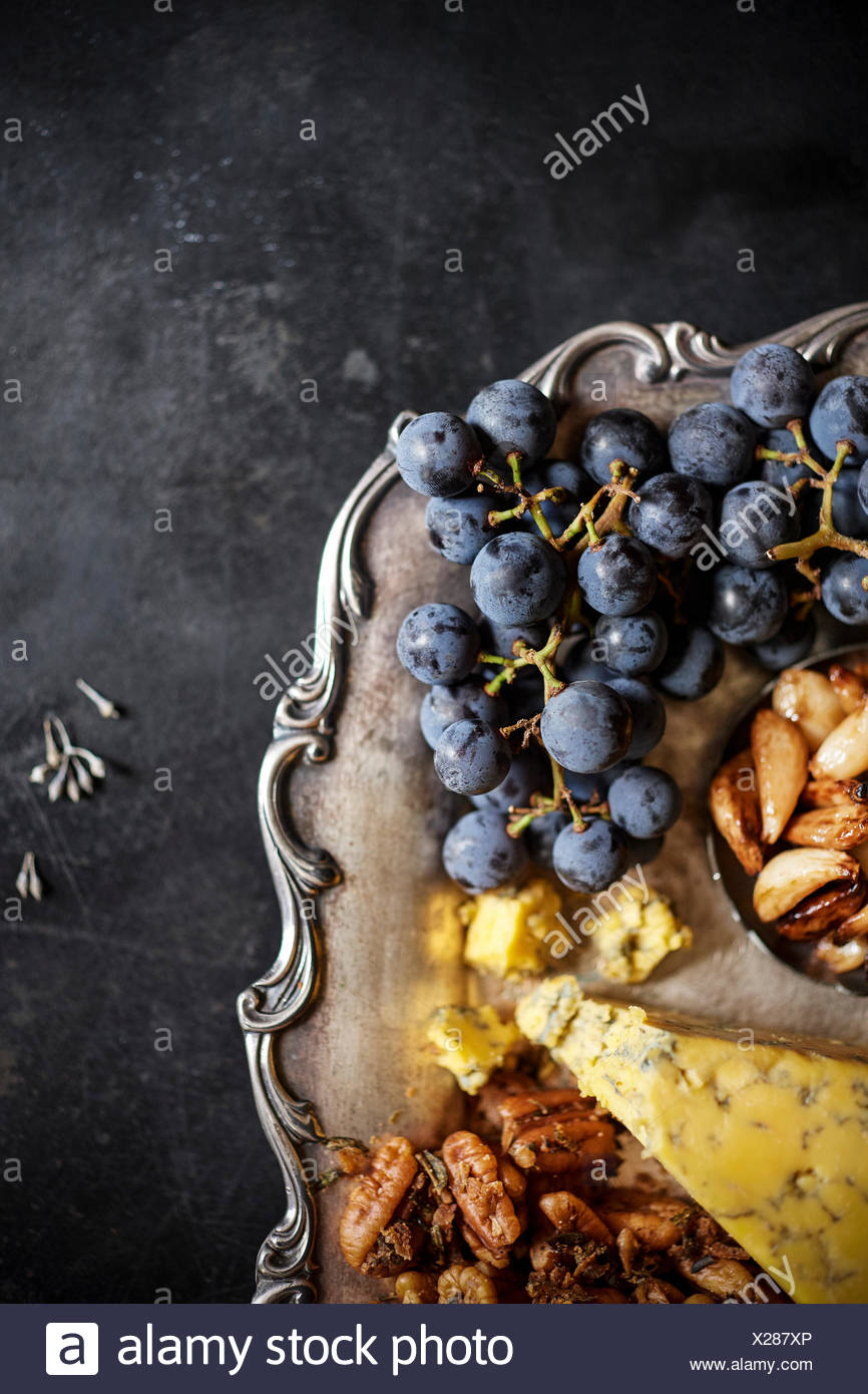 A detail macro shot of concord grapes on a charcuterie tray with blue cheese and pecans. - Stock Image