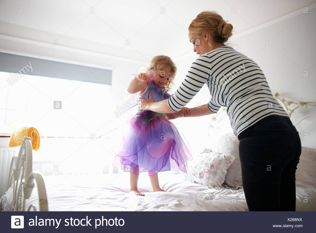 Young girl dressed in fairy costume, standing on bed, mother lifting her - Stock Image