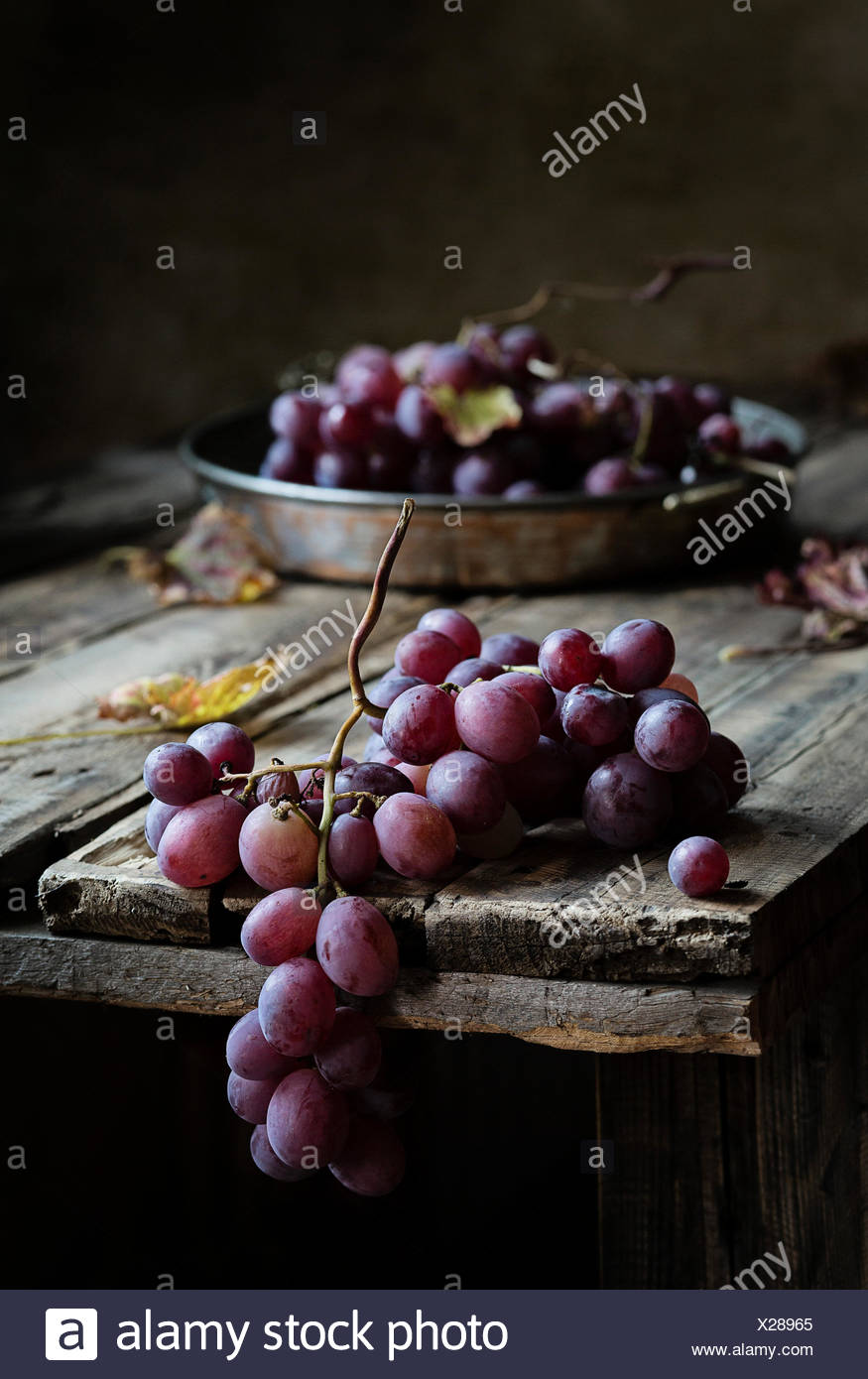 Fresh bunch of red grapes on wooden table - Stock Image