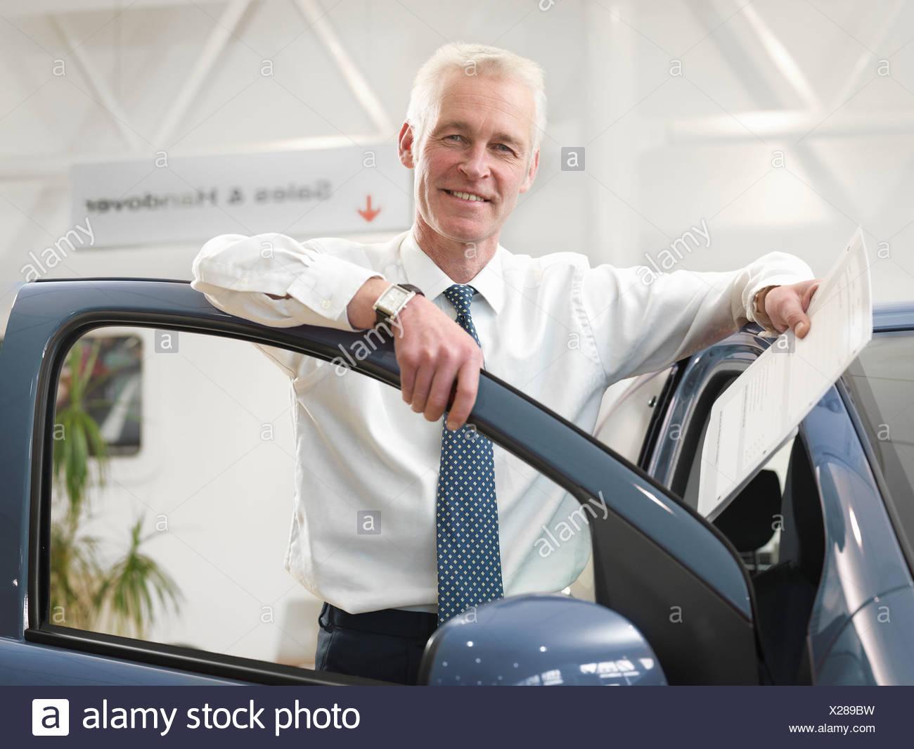 Salesman with car in car dealership - Stock Image