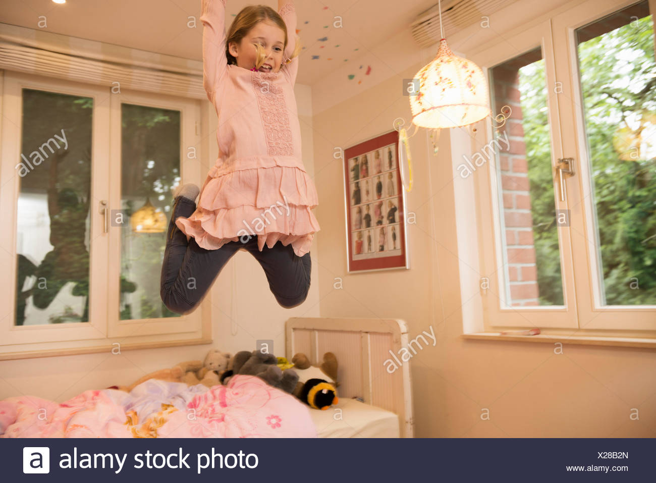 Girl having fun jumping mid air from bed in bedroom - Stock Image