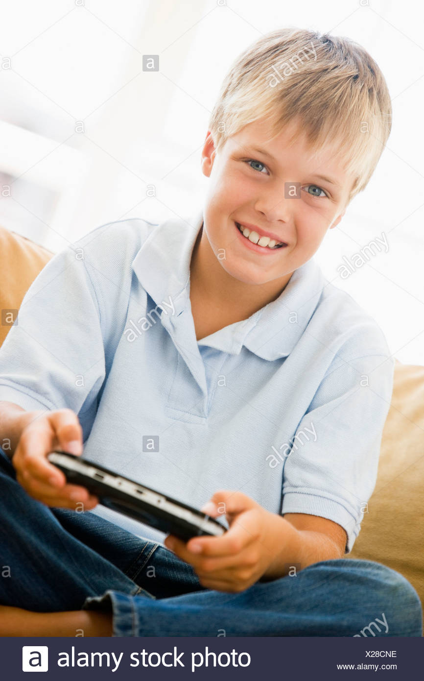 Young boy in living room with handheld video game smiling - Stock Image