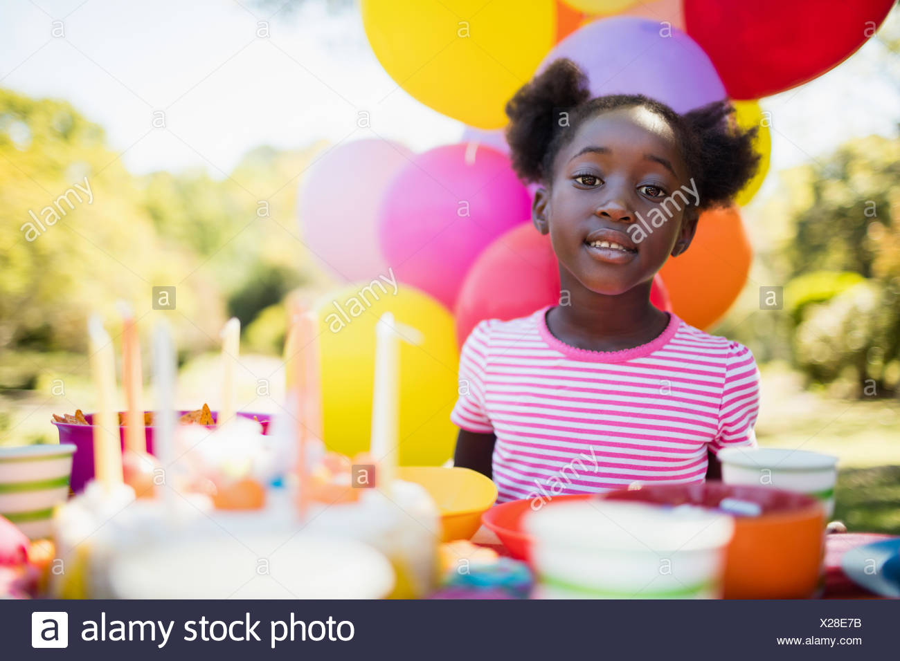 Portrait of cute girl posing during a birthday party - Stock Image